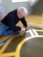 Gary, applies the clear coat to the 23K Gold Leaf on the Fair Harbor Fire Dept.  Maltese Cross logo on the floor of the meeting room