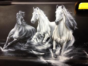 DETAIL of Horses airbrushed onto a pickup trucks tailgate.
